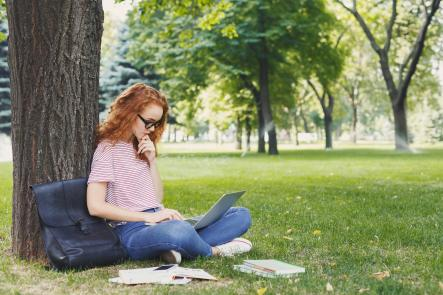 Student women stydying outside.She is sitting on the green grass in park near tree with her laptop. Next to her are her books, backpack and phone.