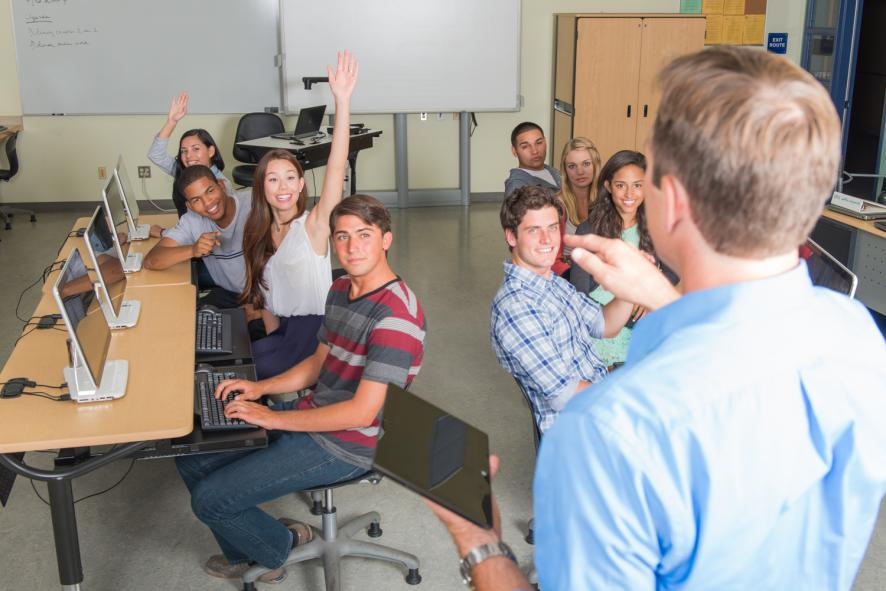 High school teacher questioning students during a lecture in the classroom.