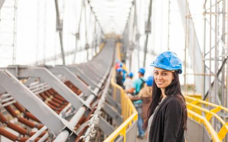Female site engineer in her 20s wearing a blue hardhat. She is standing on a bridge.