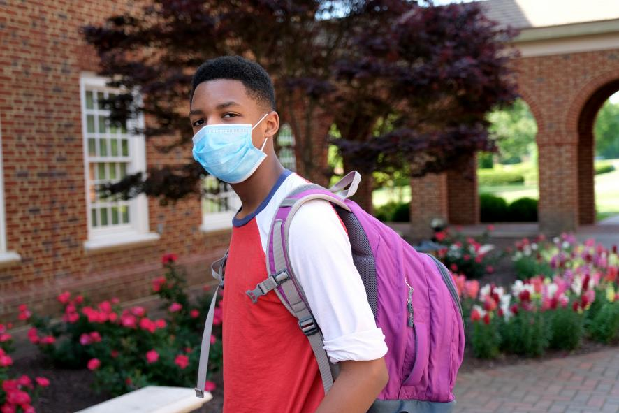 Black student going to school wearing a face mask