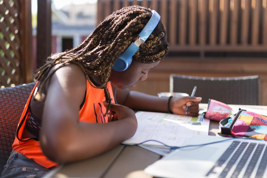 Teenager studying on the patio with earphone