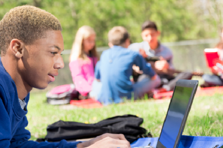 Student lying on the grass with laptop