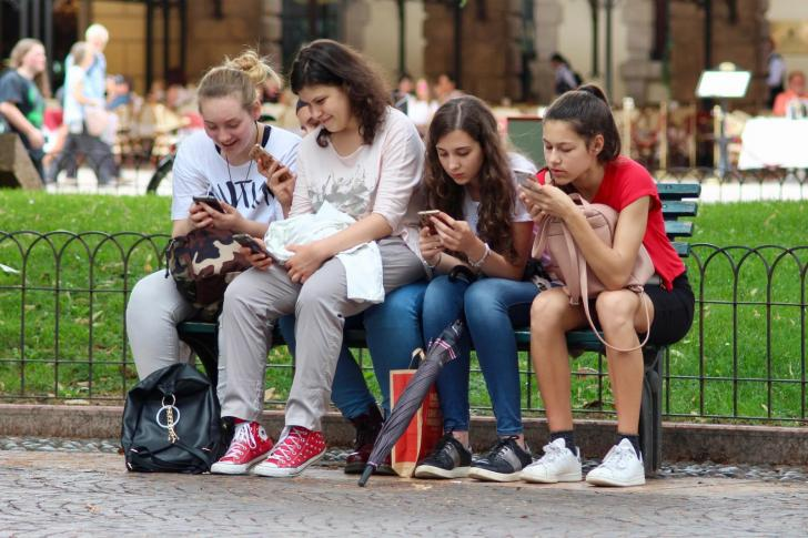 Students sitting on a banch looking at their phones