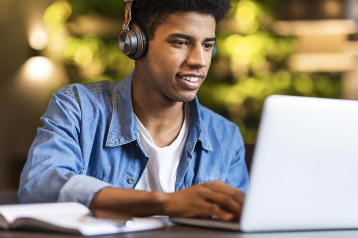 Smiling afro guy in headphones looking at laptop